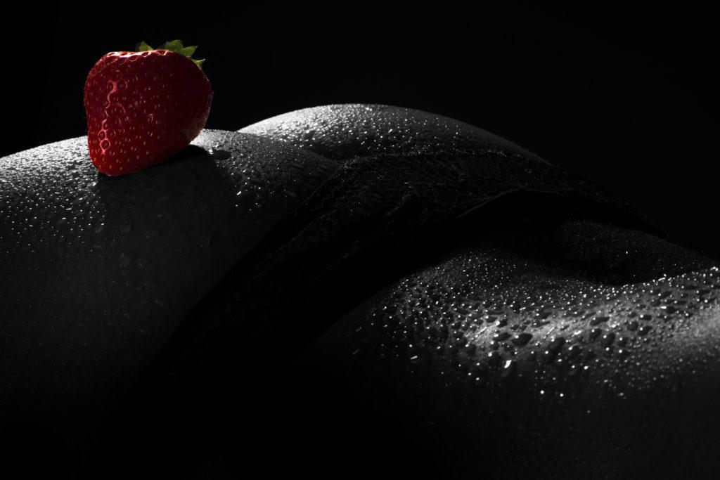 Erotisches Akt Fotoshooting: Rote Erdbeere auf sexy Hintern mit Wassertropfen